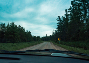 Empty road amidst trees against cloudy sky seen through windshieldの写真素材 [FYI03740121]