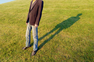 Low section of man wearing coat while standing on grassy fieldの写真素材 [FYI03740209]