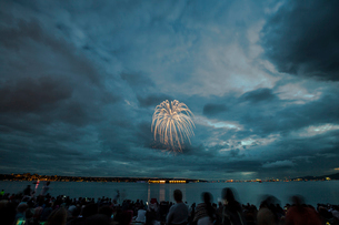 People enjoying firework display against cloudy sky over river at nightの写真素材 [FYI03740224]