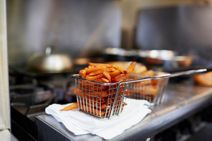 Close-up of French fries in fryer basket on kitchen counterの写真素材 [FYI03740237]