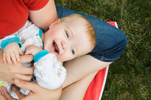 Midsection of mother tickling cheerful son while sitting with him on grassy field at backyardの写真素材 [FYI03740248]