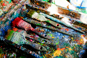 Close-up of messy paintbrushes in dirty colorful stained container on tableの写真素材 [FYI03740304]