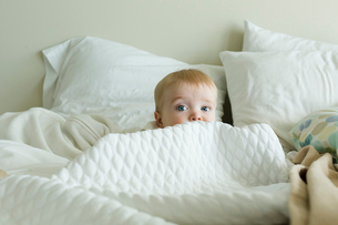 Cute baby boy hiding amidst duvet on bed at homeの写真素材 [FYI03740345]
