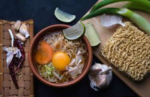 Overhead view of instant noodles soup with ingredients on tableの写真素材 [FYI03740392]
