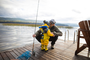 Father holding fishing rod while kissing son on wooden pier over lakeの写真素材 [FYI03740436]