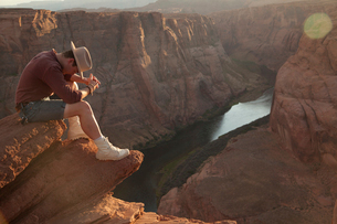 Full length of young man sitting on rock by Horseshoe Bend at desertの写真素材 [FYI03740439]