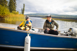 Father and son sitting in boat on lakeの写真素材 [FYI03740447]