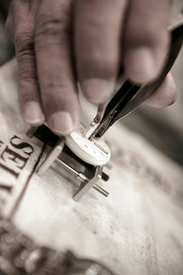 Cropped hand of man repairing watch on table at workshopの写真素材 [FYI03740462]
