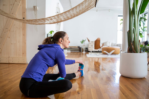 Woman exercising while sitting on floor at homeの写真素材 [FYI03740504]