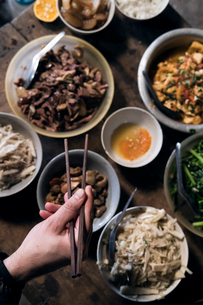 Cropped hand of woman holding chopsticks over food served on tableの写真素材 [FYI03741101]