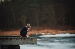 Side view of curious boy looking at river while crouching on wood at parkの写真素材 [FYI03741198]