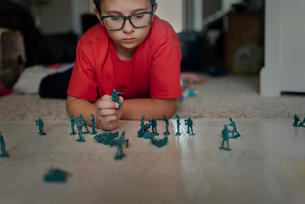Boy playing with miniature plastic toy soldiers on floor at homeの写真素材 [FYI03741358]