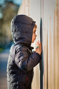 Side view of curious boy wearing hooded jacket while peeking through wooden fenceの写真素材 [FYI03741542]