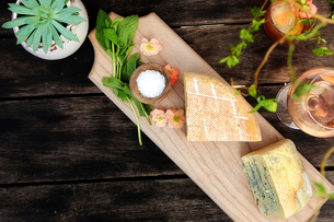 High angle view of cheese with wine and plants on wooden tableの写真素材 [FYI03741754]
