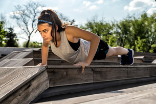 Female athlete doing push-ups on wooden seat against skyの写真素材 [FYI03741889]