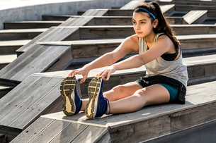 Female athlete exercising while sitting on wooden seatの写真素材 [FYI03741893]