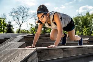 Female athlete exercising on wooden seat against skyの写真素材 [FYI03741894]