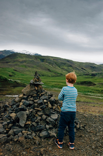 Boy standing by heap of rocks on field against cloudy skyの写真素材 [FYI03741912]