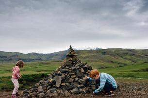Siblings playing by heap of rocks on field against cloudy skyの写真素材 [FYI03741917]