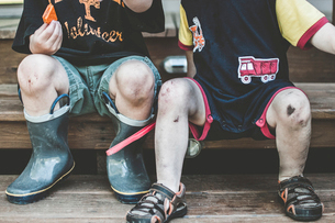 Low section of brothers with dirty legs sitting on wooden benchの写真素材 [FYI03742047]