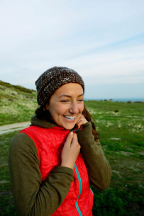 Cheerful young woman zipping jacket while standing on fieldの写真素材 [FYI03742155]