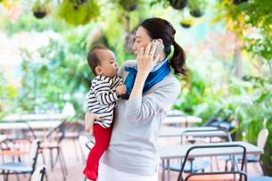 赤ちゃんを抱きかかえながら通話する女性の写真素材 [FYI03742337]