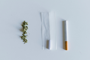 Overhead view of marijuana joints and cigarette with paper on white tableの写真素材 [FYI03742356]