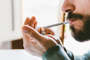 Midsection of bearded man igniting marijuana joint with cigarette lighter at homeの写真素材 [FYI03742365]