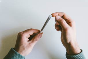 Cropped hands of man making marijuana joints over white tableの写真素材 [FYI03742367]