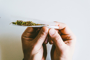 Cropped hands of man rolling marijuana joints in paper over white table at homeの写真素材 [FYI03742368]