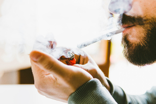 Midsection of bearded man smoking marijuana joint at homeの写真素材 [FYI03742373]