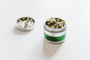 Close-up of marijuana in metallic grinder on white tableの写真素材 [FYI03742377]