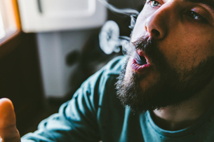 Close-up of bearded man exhaling smoke while smoking marijuana joint at homeの写真素材 [FYI03742379]