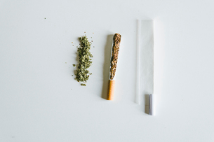 Overhead view of marijuana joints and cigarette with paper on tableの写真素材 [FYI03742383]