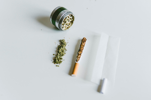 Overhead view of marijuana joints, cigarette with paper and grinder on white tableの写真素材 [FYI03742389]