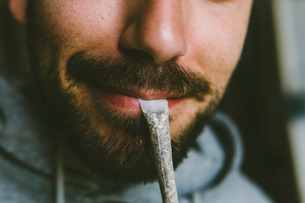 Midsection of bearded man carrying marijuana joint in mouthの写真素材 [FYI03742395]