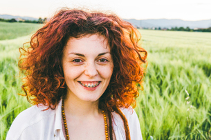 Portrait of smiling woman with redhead standing at farm against skyの写真素材 [FYI03742465]
