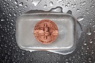 Overhead view of bitcoin in ice on wet metallic tableの写真素材 [FYI03743198]