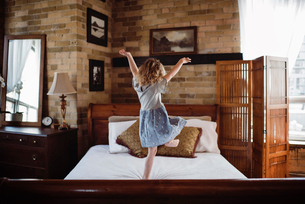 Rear view of girl with arms raised jumping on bed at homeの写真素材 [FYI03743203]