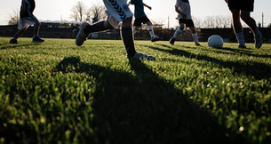 Low section of man playing soccer with children on grassy field at park during sunsetの写真素材 [FYI03743248]