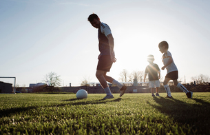 Low angle view of man playing soccer with children on grassy field against clear sky during sunsetの写真素材 [FYI03743255]