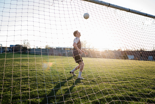 Man practicing soccer at park seen through net during sunsetの写真素材 [FYI03743268]