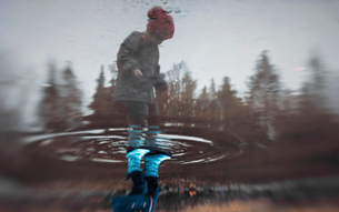 Low section of girl standing on puddle during rainy seasonの写真素材 [FYI03743679]
