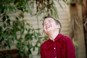 Close-up of happy boy laughing while standing against wall at yardの写真素材 [FYI03743730]
