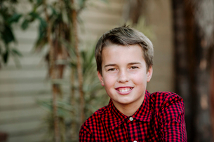 Close-up portrait of smiling boy standing against wall at yardの写真素材 [FYI03743732]
