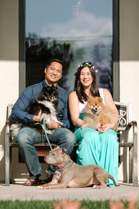 Portrait of confident smiling couple with dogs sitting on bench against houseの写真素材 [FYI03743793]