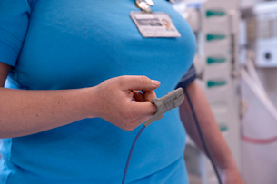 Midsection of female doctor using pulse oximeter in hospitalの写真素材 [FYI03743942]