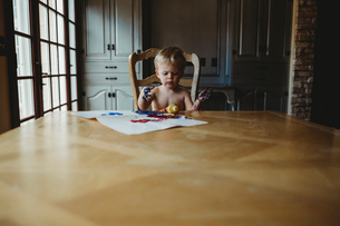 Shirtless baby boy with dirty hands sitting by wooden table at homeの写真素材 [FYI03744017]
