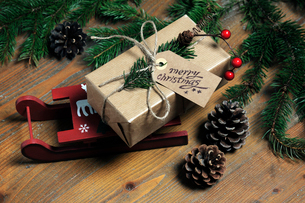 High angle view of Christmas present with decorations on wooden tableの写真素材 [FYI03744063]