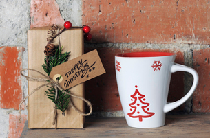 Close-up of Christmas present with mug on wooden table by brick wallの写真素材 [FYI03744067]